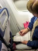 Lisa doing a crossword on the plane to Johannesburg